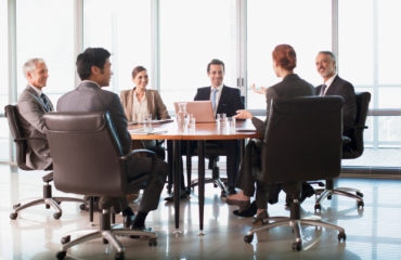 Business people meeting at table in conference room --- Image by © Ocean/Corbis